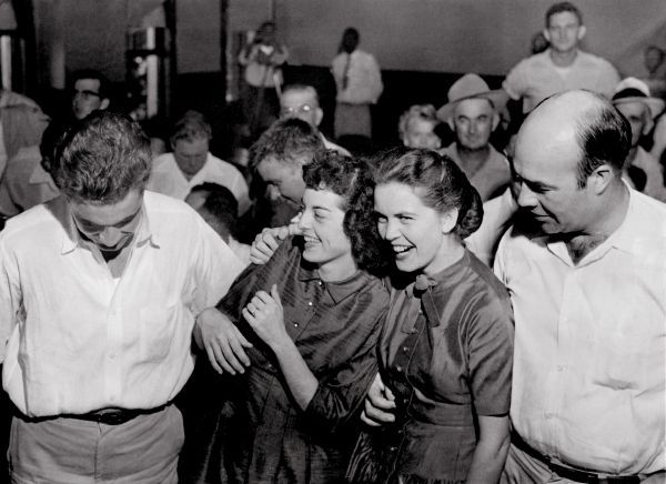 "Mr. & Mrs. Roy (Carolyn) Bryant (left) with Mr. & Mrs. J.W. Milam showed happiness at a the verdict delivered in Sumner, Miss. Friday, September 23, 1955. Roy Bryant and J.W. Milam were acquitted in the murder of Emmett Till. In February, 2007, a Leflore County grand jury declined to indict Carolyn (Bryant) Donham on criminal charges. The Chicago youth was killed for allegedly wolf whistling at Mrs. Roy Bryant at a store owned by her husband in Money, Miss. in August 1955. His body was pulled from the Tallahatchie River near Phillip on August 31. He had been beaten and shot once in the head. A 70-pound cotton gin fan was tied with barbed wire around his neck. The district attorney in rural Leflore County, Miss. had sought a manslaughter charge against Carolyn Bryant Donham, who was suspected of pointing out to her husband to punish the boy, but a February 2007 grand jury refused to bring any new charges. (Courtesy Special Collections / University of Memphis Libraries) ( Following excerpted from The Commercial Appeal Sept. 24, 1955 1A story by William Sorrells ) ""I feel a lot better,"" the attractive 21-year-old mother (Mrs. Roy Bryant) sighed, leaning on the shoulder of her stocky husband, a former paratrooper. ""We feel so good,"" Bryant chimed in. They smiled happily as photographers took over. Milam reached over, pulled his pretty wife to his shoulder. ""I feel fine,"" he said. ""But I'm going to get me a wig."" There was testimony throught the trial about ""a big bald-headed man."""